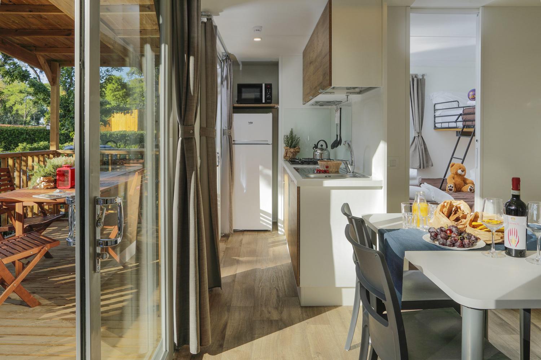 Zona living in casa mobile con tavolo, cucina e veranda