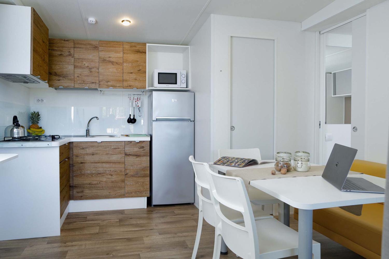 Soggiorno con cucina, frigorifero e tavolo in casa mobile