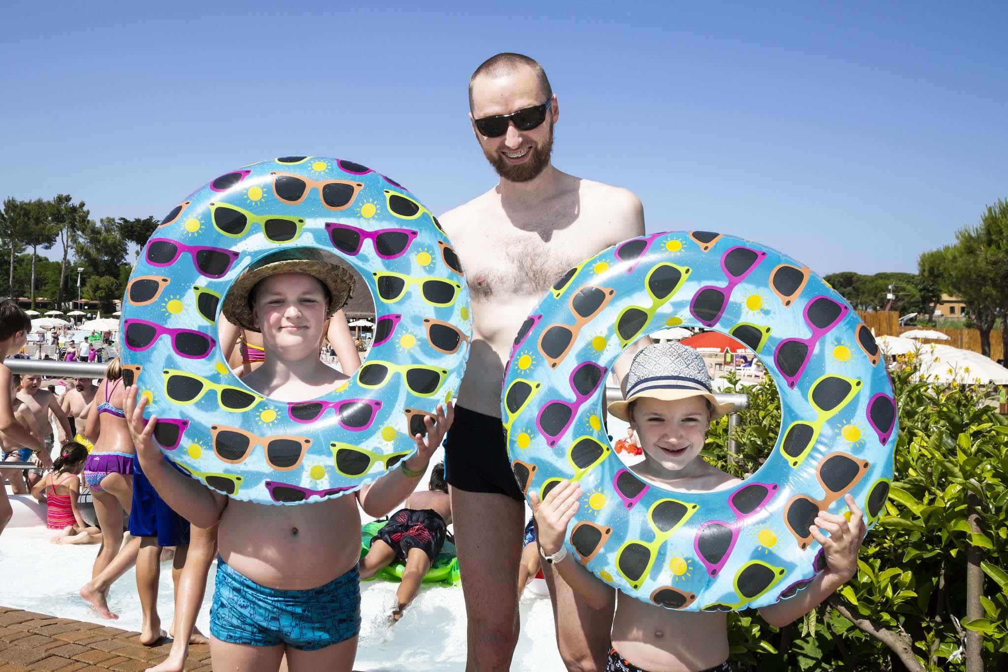 Famiglia in piscina con gonfiabili, ciambelle