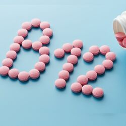 Pillole di Vitamina B12 Rosa su Sfondo Azzurro che Escono da un Contenitore Bianco
