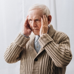 Un Anziano che Soffre di Demenza Senile si Tocca la Testa