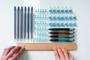 Mani con un righello che misurano le distanze tra oggetti di cancelleria