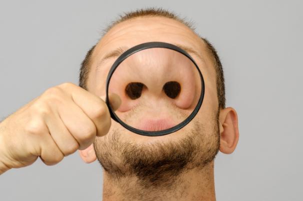Un uomo odora l'ambiente senza recepire gli odori, mentre una lente di ingrandimento sottolinea l'apertura delle sue narici