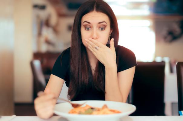 Una donna elegante si porta la mano alla bocca perché non si sente bene dopo aver ingerito un cibo al quale è allergica o intollerante