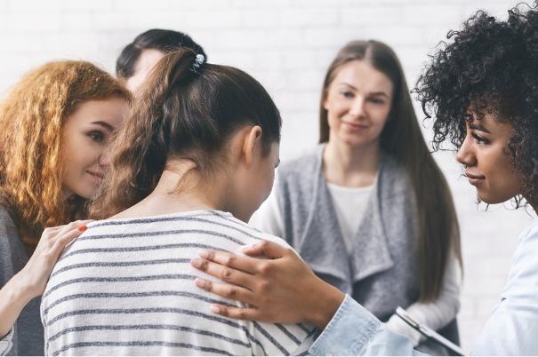 Un gruppo di ragazze di etnie e aspetto differente sono sedute in cerchio e si sostengono in una seduta di terapia di gruppo