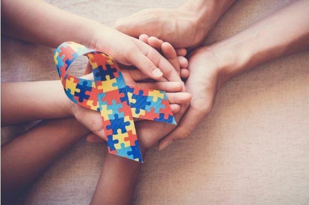 Fiocco con Puzzle Colorato Simbolo dell'Autismo Stretto in Mani di una Famiglia Caregiver di un Autistico