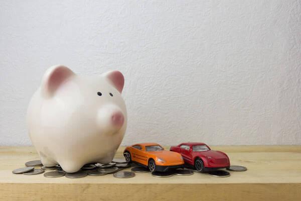 Skarbonka i dwa samochody zabawki jako metafora kredytu na samochód