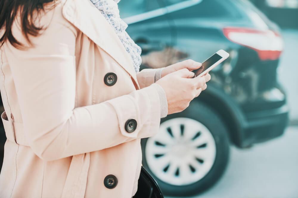 Kobieta z telefonem stoi przy samochodzie