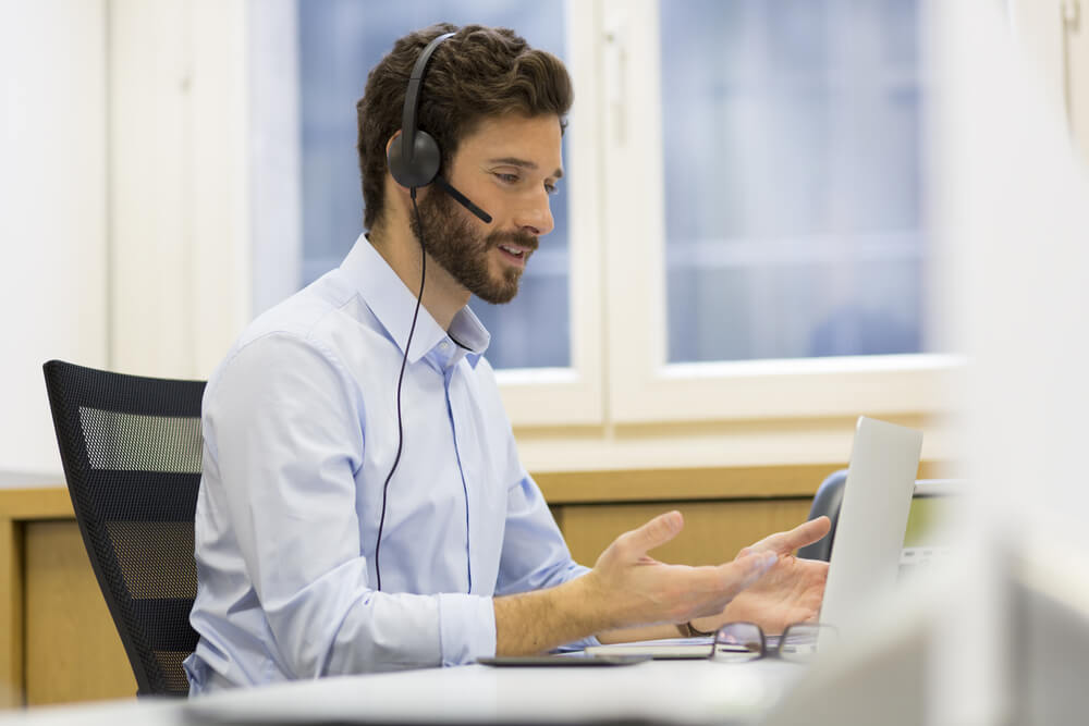 Mężczyzna przy biurku rozmawiający przez słuchawkę