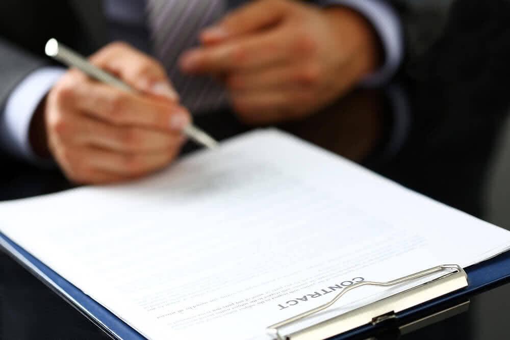 Mężczyzna podpisuje umowę