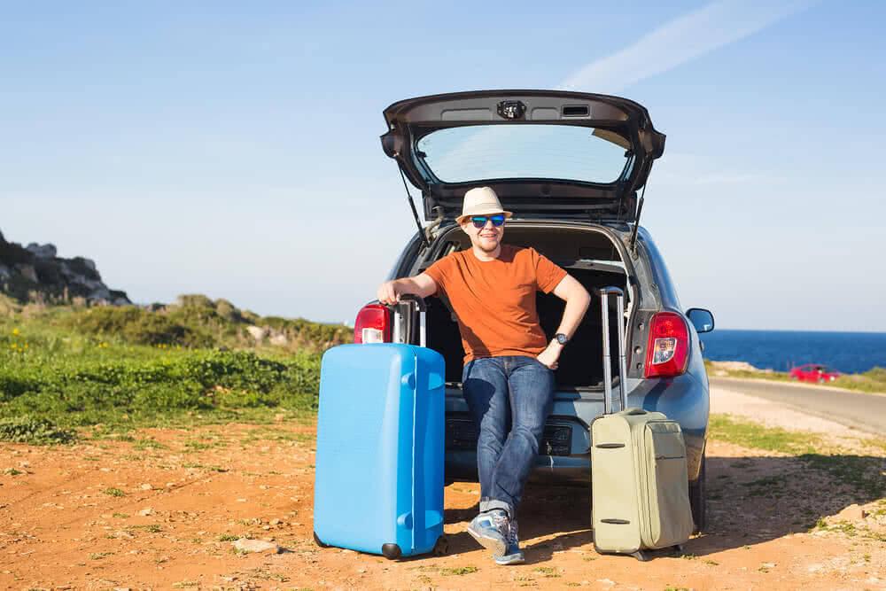 Mężczyzna z walizkami stoi przy otwartym samochodzie