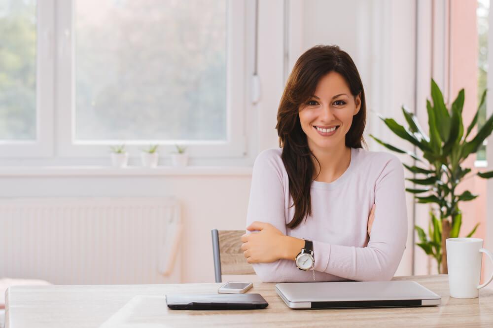 Uśmiechnięta kobieta siedzi przy stole