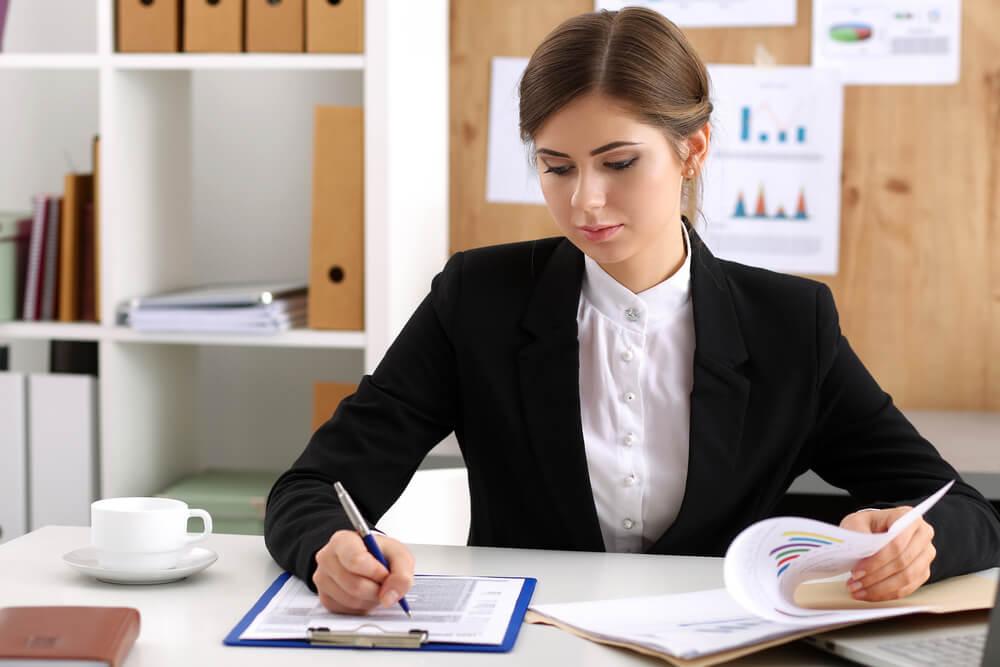 Kobieta sprawdza umowę zlecenia przed kredytem