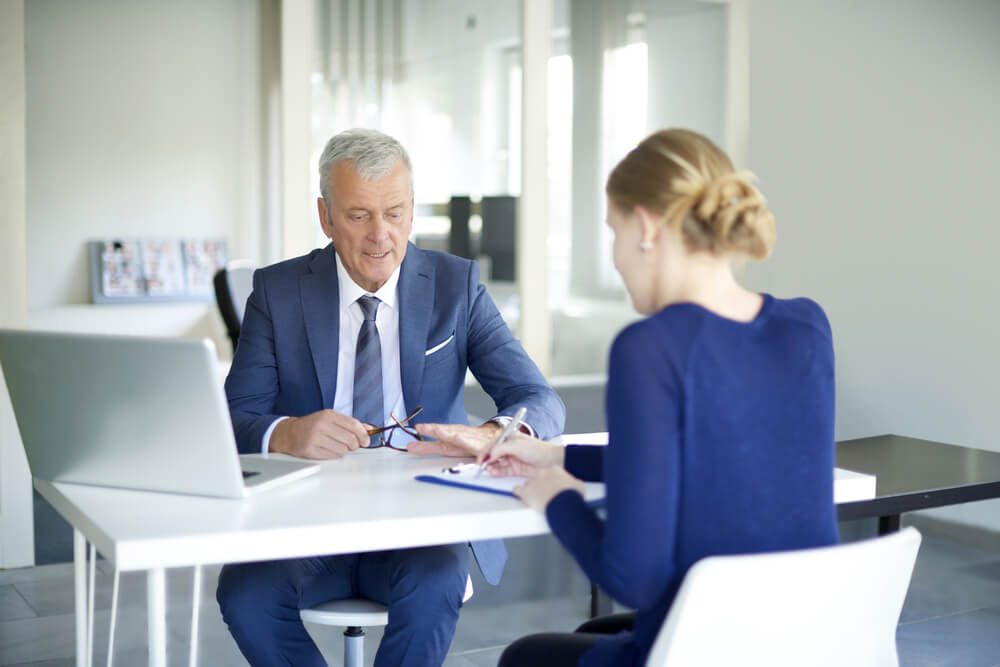 Pracownik wyjaśnia klientowi czym są walutowe kredyty hipoteczne