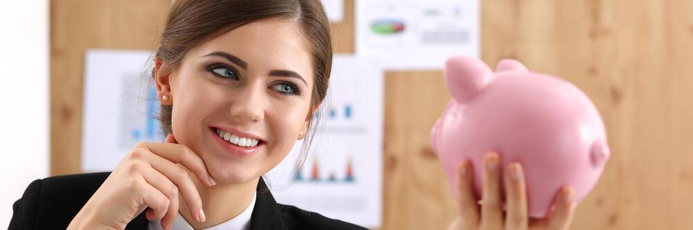 Kobieta trzymająca skarbonkę na oszczędności w celu wcześniejszej spłaty kredytu