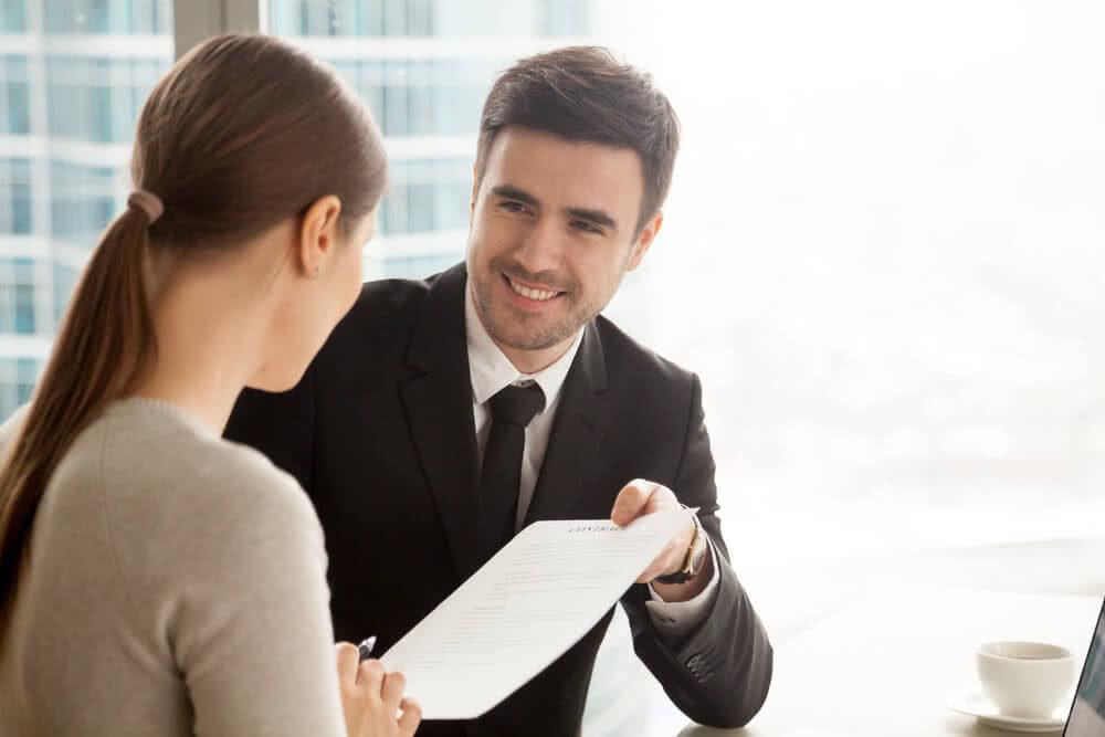 Pracownik banku wręcza symulację kredytu klientowi hipotecznego klientowi
