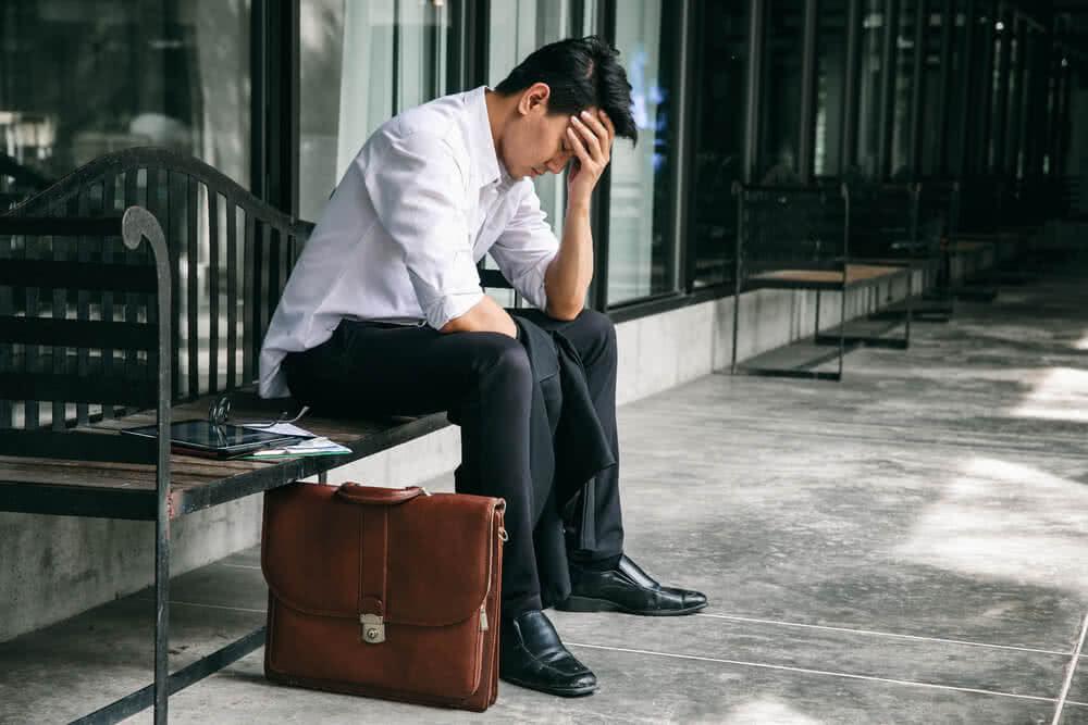 Zwolniony z pracy mężczyzna trzyma dokument z ubezpieczeniem dla bezrobotnych