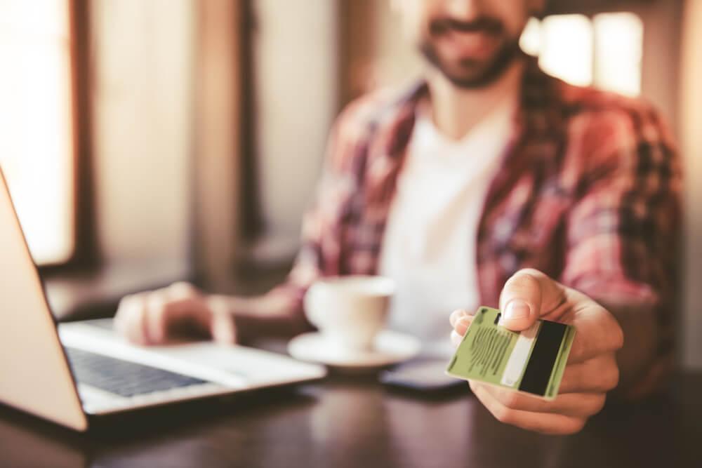 Mężczyzna dokonujący przelewu internetowego przy użyciu karty z kodem IBAN
