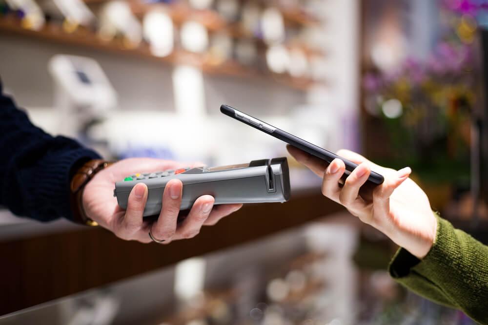 Mężczyzna dokonuje płatności telefonem przy użyciu technologii NFC