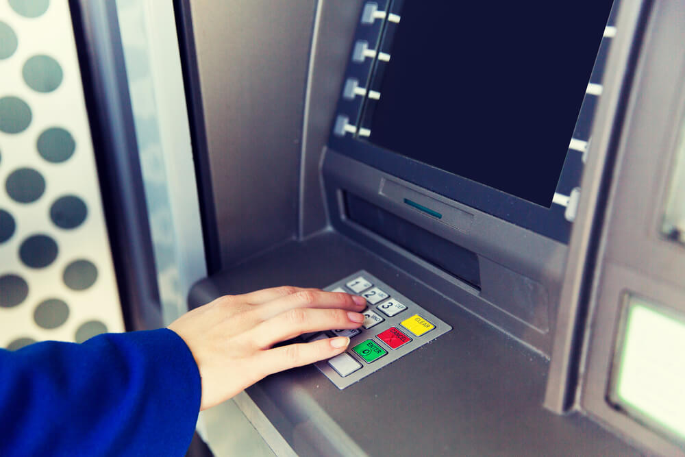 Kobieta wypłaca pieniądze z bankomatu bez udziału karty