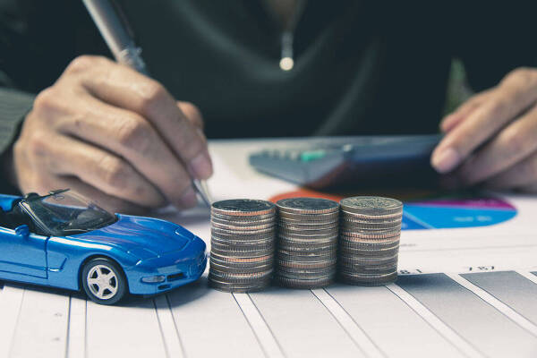 Samochodzik obok monet jako symbol ubezpieczenia AC