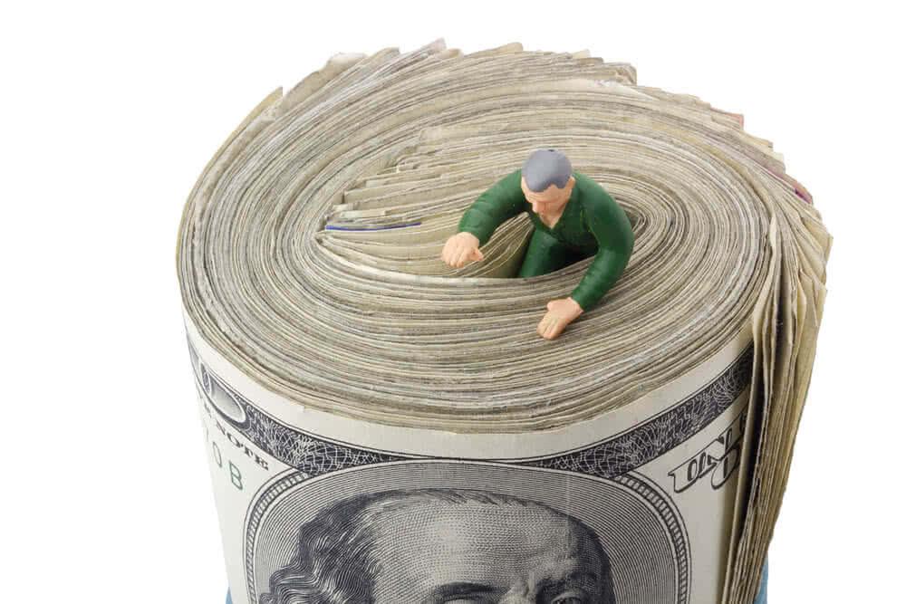 Mężczyzna w spirali pieniędzy jako metafora ryzyka kredytowego