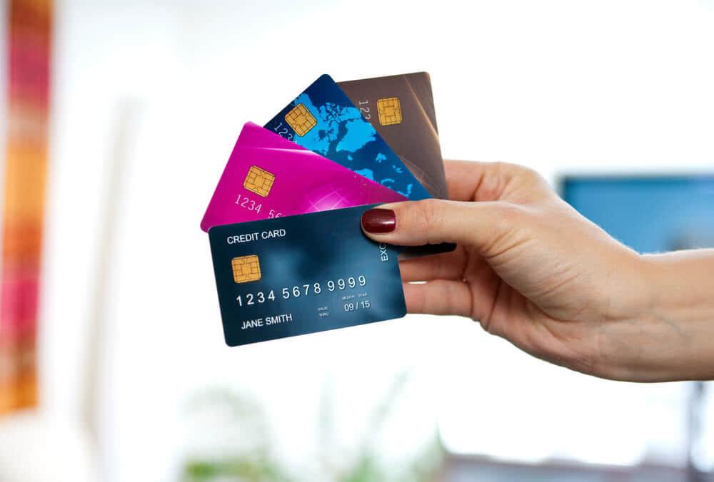 Kobieta trzyma cztery różne karty, w tym debetową i kredytową