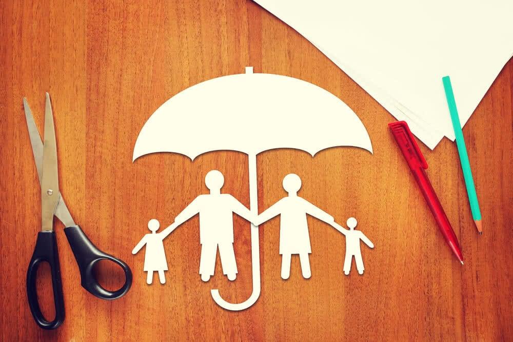 Rodzina pod parasolem będącym symbolem polisy ubezpieczeniowej