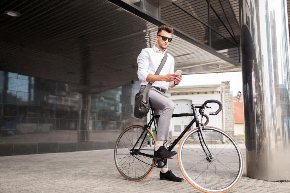 Mężczyzna na rowerze ubezpiecza swój pojazd przez telefon
