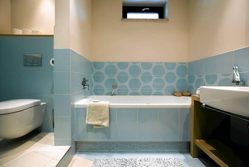 W łazience pełniącej również funkcję toalety warto wydzielić intymną strefę na kącik z sedesem - oczywiście jeśli pozwala na to metraż i kształt pomieszczenia. Można na przykład zbudować ściankę albo zamontować przegrodę z tafli szkła. Wnętrze stanie się wtedy bardziej funkcjonalne.<br/> Łazienkę wykończono w błękicie, - gospodarze uwielbiają ten kolor, a nie pasował do żadnego innego pomieszczenia.