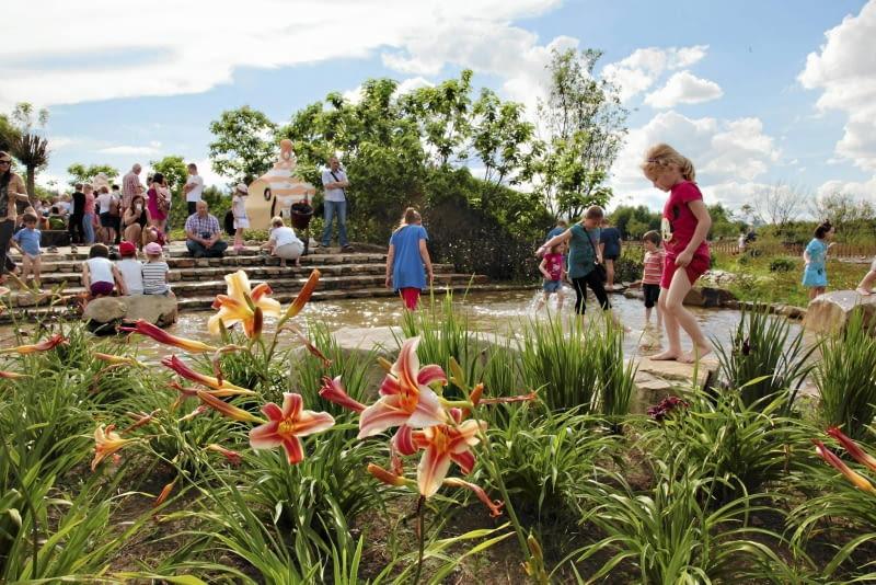 PŁYTKI STRUMIEŃ otoczony kępami tataraku i kwitnących liliowców zachęca do taplania się w wodzie.