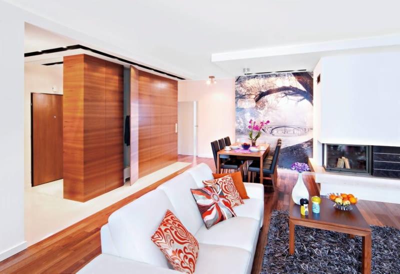 Gospodarze, którzy lubią przestronne i jasne wnętrza, zdecydowali się połączyć salon z przedpokojem i kuchnią. Uzyskanej w ten sposób strefy dziennej nie zamierzali zagracać masywnymi wolno stojącymi meblami do przechowywania. Z drugiej strony zdawali sobie sprawę, że są one w domu konieczne. Dylemat rozwiązała projektantka, proponując zbudowanie meblościanki, która oddzieliłaby strefę wypoczynkową od przedpokoju, a jednocześnie zapewniła wygodne schowki. Pojemną szafę, sięgającą od podłogi do sufitu, zrobiono z płyty fornirowanej egzotycznym tekiem (z tego samego drewna jest parkiet).