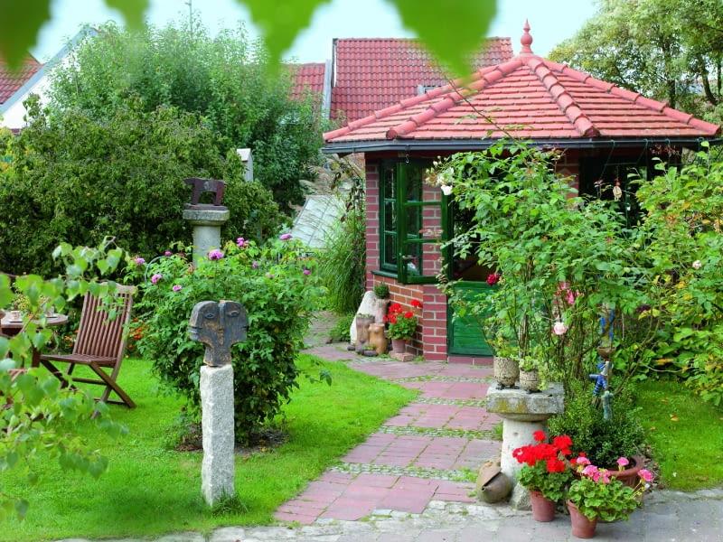 Gepflasterter Weg zum Gartenhaus, Rosa ( Rosen ), Pelargonium ( Geranien ) in Tpfen, Sitzplatz auf dem Rasen, getpferte KunstobjekteBezug : www.ton-art-jmp.de Tel.: 08752-168761039806, 61039807