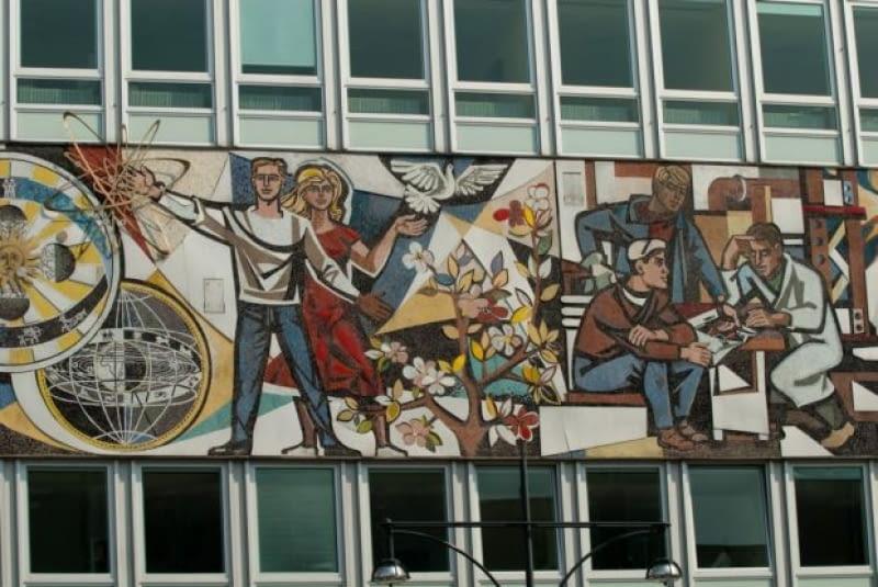 Mozaika opasująca Dom Nauczyciela przedstawia różne aspekty życia w NRD - od sportu, poprzez naukę, wojsko, przemysł po rekreację. Zwraca uwagę wyrazista, socrealistyczna stylizacja rysunku.