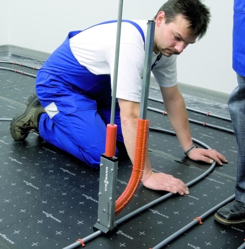 Rury grzejne wodnego ogrzewania podłogowego mocowane do maty systemowej klipsami za pomocą specjalnego przyrządu