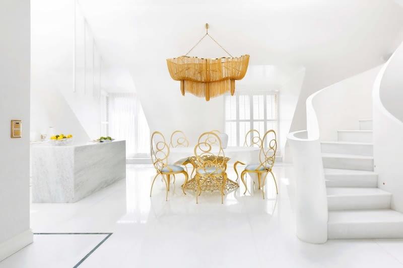 Jadalnia jest wyspą złotego ażuru na marmurowej tafli posadzki. Wokół unikatowego stołu Mondrian Art Form o podstawie ze złoconych metalowych krążków, krzesła Ghirigori (oba modele marki Cantori).