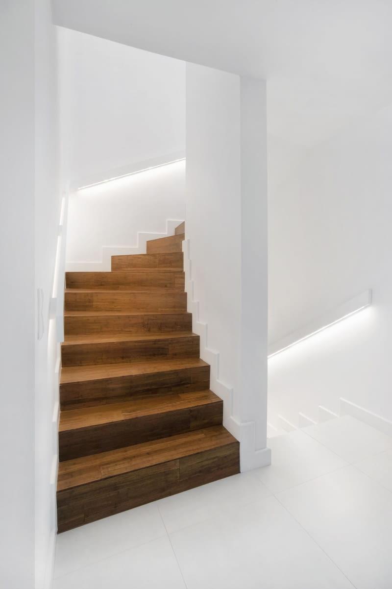 Betonowe schody zabiegowe prowadzące na piętro zostały obłożone drewnem. Zastosowanie takiego materiału w ciemnym kolorze w połączeniu z bielą ścian sprawia, że ten fragment wnętrza jest elegancki i nowoczesny zarazem