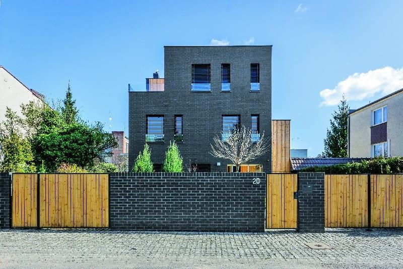 Pierwotnie na parceli stał niewielki budynek, który łączył się ścianą z sąsiednim. To, co zwykle uznawane jest za niedogodne (mało kto lubi bliźniaki), zostało w projekcie nowo powstałego domu obrócone na korzyść inwestorów - architekci wykorzystali każdy metr powierzchni działki