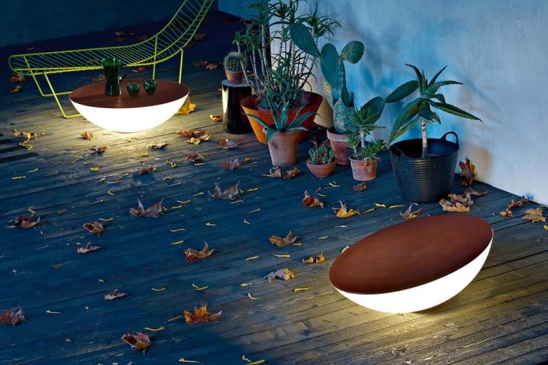 Lampa-stolik. Nieprzepuszczająca światła pokrywa, wyprofilowana w taki sposób, że woda ścieka z niej na boki, może służyć za blat. Ponadto lampa Solar emanuje miękką poświatą, budując klimat miejsca. Dzięki specjalnej konstrukcji całość można przechylać i sterować kątem padania światła. Foscarini, fabrykaform.pl