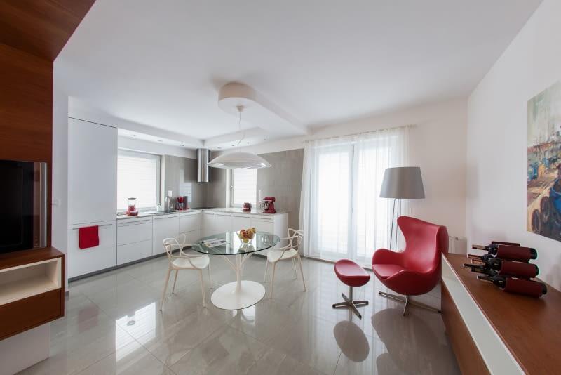 W salonie znajduje się kultowy fotel 'Egg' autorstwa Arne Jacobsena w ulubionym kolorze właścicielki - intensywnej czerwieni.