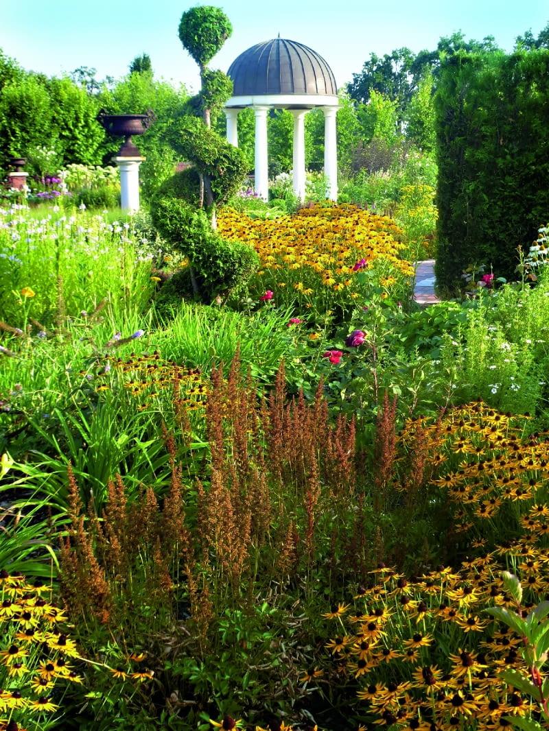 Ogród romantyczny ze świątynią dumania późnym latem zyskuje słoneczną oprawę - rozkwitają łany rudbekii.