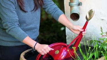 OFrau schpft Wasser aus WasserfassGiekanne : Garpa Tel. 0 41 52 / 92 52 00