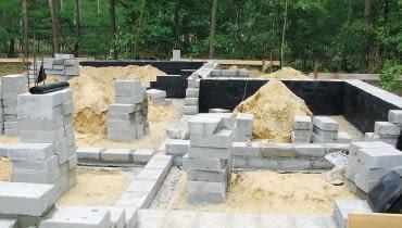 Ściany fundamentowe zwykle wykonuje się z bloczków betonowych. Ich powierzchnie zabezpiecza się masami asfaltowo-kauczukowymi.