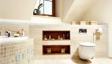 Przykład 1. Szerokie półki pod skosami zbudowano z płyt gipsowo-kartonowych. Wykończono je takim samym trawertynem jak ściany. Wnęki obłożono odpornym na działanie wilgoci drewnem tekowym.