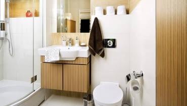 NA STRAŻY PORZĄDKU. Pomieszczenie jest dość małe, dlatego projektantki od razu zaproponowały, by zainstalować w nim kabinę prysznicową zamiast wanny (mniejszy jej model w ogóle nie wchodził w grę, bo obydwoje właściciele są wysocy). Dzięki temu udało się zaoszczędzić sporo miejsca, które można było przeznaczyć na meble służące do przechowywania zapasów środków czystości i innych akcesoriów. I tak znalazły się tu dwie wolno stojące szafy oraz szafka pod umywalkę. Płytki ceramiczne, którymi wyłożono wnęki i fragmenty ścian, zostały idealnie dopasowane do wzoru okleiny na łazienkowych meblach - mają tylko jaśniejszy odcień niż ona (projekt wnętrza: Weronika Steffen-Lotarska, Olga Werikowska).