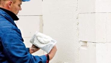 Ściany domu dobrze jest tynkować w kilka miesięcy po jego wymurowaniu, tak żeby budynek zdążył osiąść