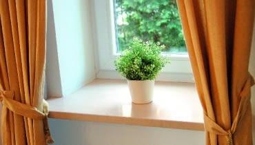 Marmurowy parapet o prostej formie zamontowany we wnęce okiennej