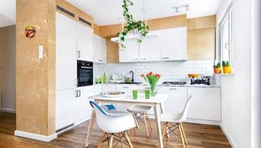 NA WYMIAR. W małej kuchni świetnie sprawdza się rozkładany stół (z Ave Art). W kuchennej zabudowie oprócz niezbędnych sprzętów zmieściła się także pralka (pod oknem). Zabytkową wagę Beata odziedziczyła po babci. Jesionowe deski na podłodze są z firmy Parkiet Hajnówka.