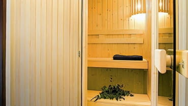 <B>Nie wszyscy miłośnicy sauny mogą sobie pozwolić na kupienie gotowej kabiny. Nie znaczy to jednak, że muszą całkowicie zrezygnować z tej formy relaksu w domu. Sauna zrobiona na zamówienie kosztuje znacznie mniej. Ta zaprezentowana na zdjęciach została zaaranżowana w niedużym pomieszczeniu gospodarczym.</B> <BR >ŁAZIENKA Z SAUNĄ. Do budowy sauny można wykorzystywać tylko gatunki drewna odporne na wilgoć i na zmiany temperatury: świerk skandynawski, osikę, olchę, jodłę kanadyjską i cedr kanadyjski. Najlepsze jest abachi, o jednolitym kremowo-żółtym odcieniu. Do oświetlenia używa się światłowodów przeznaczonych specjalnie do saun i łaźni parowych. Tę saunę zbudowano ze świerku, wyposażenie - z osiki. Drzwi są z przyciemnianego hartowanego szkła.