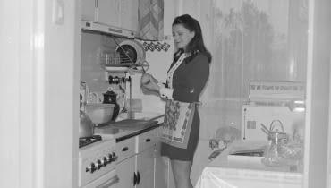 Danuta Krotowicz obiera gruszkę w kuchni. Widoczna kuchenka gazowa 'Warta', zlew i suszarka do naczyń.
